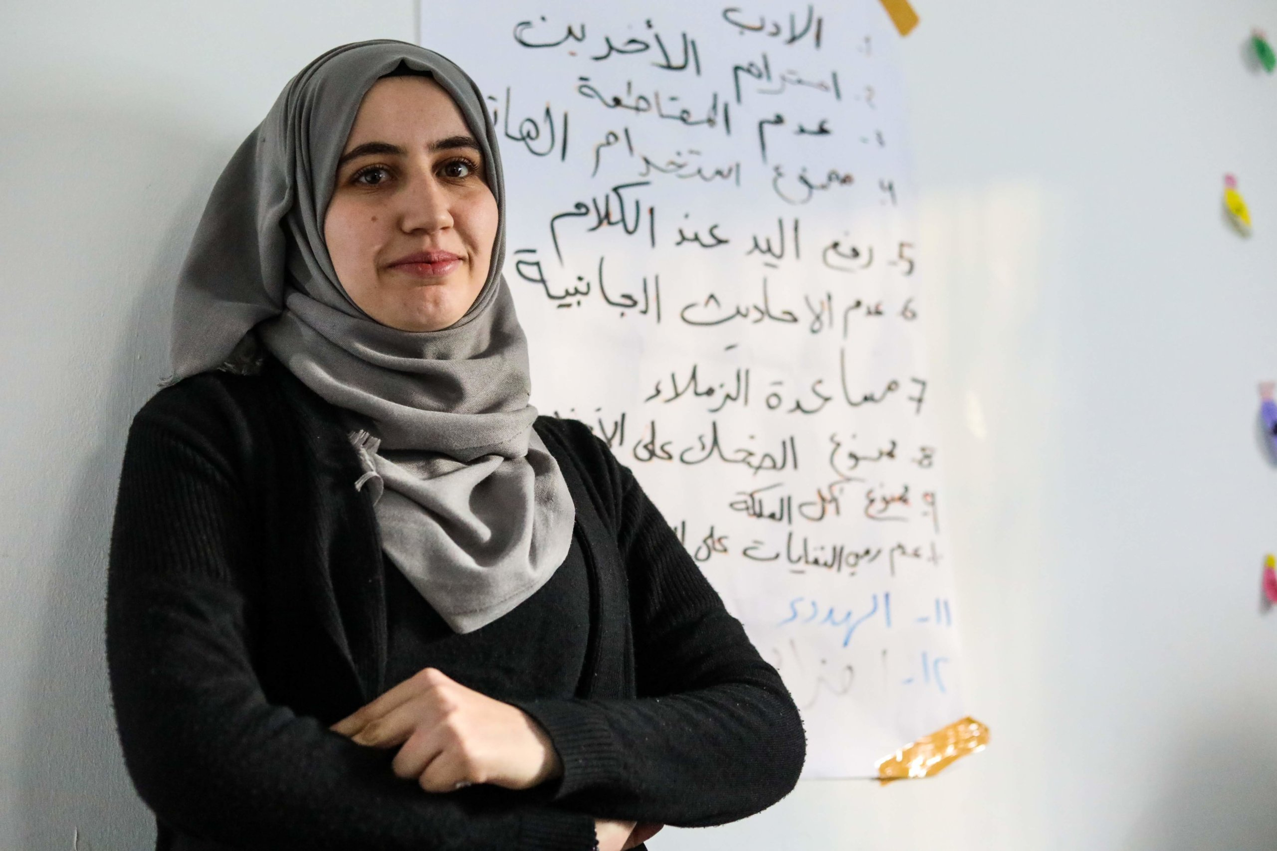 Refugee student stands at whiteboard with arabic text in study centre